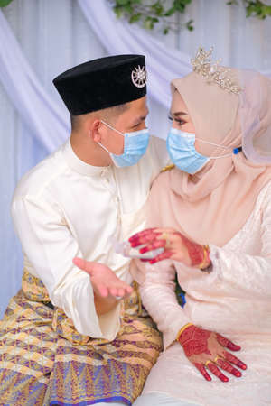 A muslim couple pose  in medical face masks during coronavirus pandemic. COVID-19 weddings. Stay Safe  . Stock Photo - 151537754