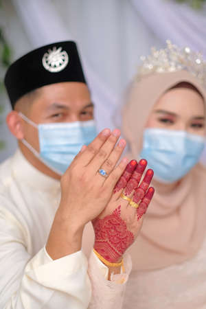 A muslim couple pose in medical face masks during coronavirus pandemic. COVID-19 weddings. Stay Safe .
