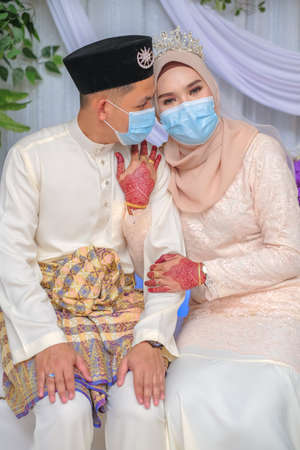 A muslim couple pose  in medical face masks during coronavirus pandemic. COVID-19 weddings. Stay Safe  . Stock Photo - 151537762
