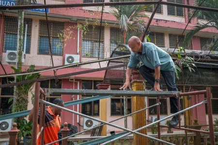 Muadzam Shah, Malaysia- July 7th, 2020: Two workers assembling scaffolding before start roof framework