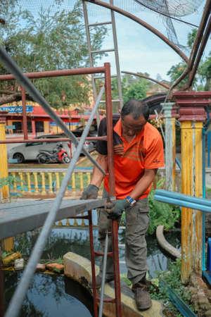 Muadzam Shah, Malaysia- July 7th, 2020:  Worker assembling scaffolding before start roof framework Publikacyjne