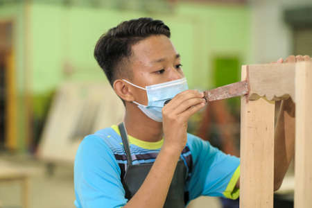 Young carpenter in work clothes and face mask  using wood filler in finishing work  for console table . 版權商用圖片