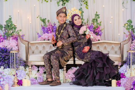 Indoor shooting for Malay wedding, the bride and groom wearing Malay traditional cloth in marriage ceremony . Happy & Family Concept