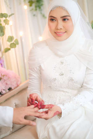 Malay wedding couple putting a ring on hand. Selective focus and shallow DOF.