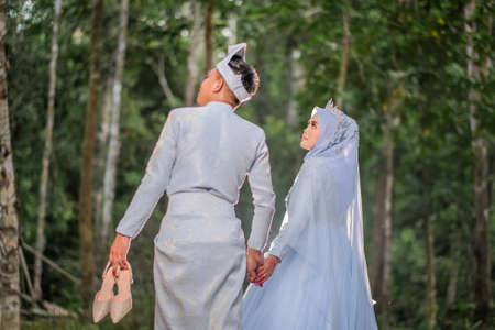 Wedding photo shooting. The bride and groom wearing baby blue Malay traditional cloth at the forest.