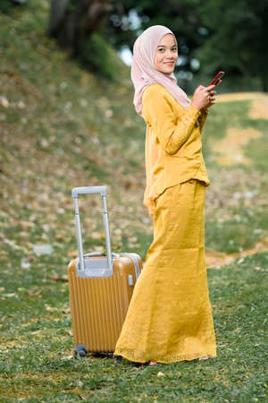 Gorgeous smiling muslim woman in traditional wear holding smartphone and luggage at lake garden.