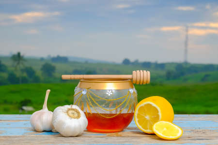 Fresh honey in glass jar , garlic and lemon on old wooden with blurred background , healthy nutrition, strengthening immunity and treatment of flu