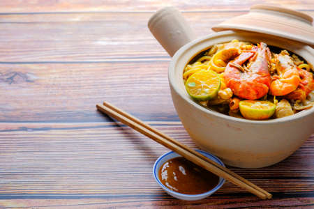 """Clay Pot """"Mee Kari """" or curry noodles with flavorful cooked Ingredients. Usually eat with fishball and fishcake. Image is a selective focus"""
