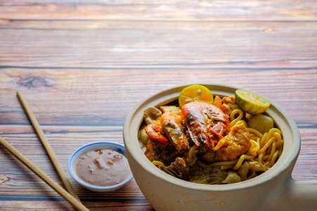 """Clay Pot """"Mee Kari """" or curry noodles with flavorful cooked Ingredients. Usually eat with fishball and fishcake. Image is a selective focus Stock Photo"""