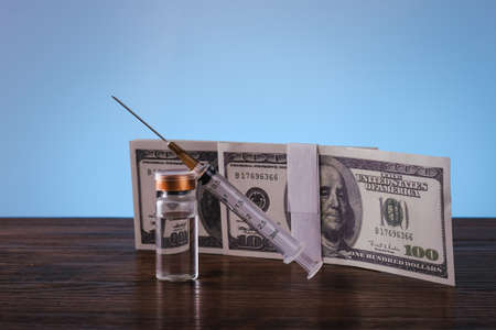 Syringe, bottle and money in budget cost money concept spend to health with light blue background