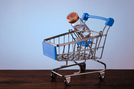 Shopping cart with vaccine bottle. On a blue background with place for text. Stock Photo