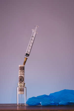Syringe , glove, bottle and money in budget cost money concept spend to health with light blue background
