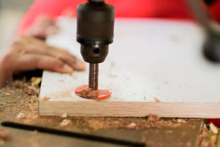 The carpenter is using a bench drill to fasten the hinge screws on to the wooden door. Stock Photo