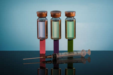 A Vaccine in vial and syringe close-up on a  glass table, medical concept, laboratory, subcutaneous injection vaccination, dose. Disease treatment immunization.