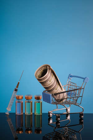 Shopping cart , syringe, money and  vaccine bottle on a blue background with place for text. Stock Photo