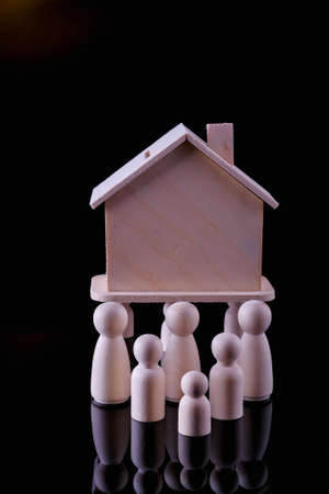 Business, Finance, Home loan and management concept. Close up of wooden people figure standing on glass table with  mini wooden house toy on black background.