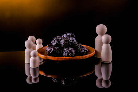 Ramadan Kareem Festival, Dates at wooden bowl with wooden firgures standing on black background