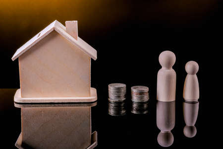 Business, Money, Finance, Home loan and management concept. Close up of wooden people figure standing on glass table with coins and mini wooden house toy on black background.