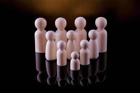 Wooden figurines of the family stand on a black background. The concept of a classic traditional family. values, unity, loyalty, strong and healthy. Cell society, procreation and gene pool.