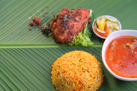 Nasi Beriyani , Gulai Kawah and Ayam Berempah served on green leaf. Stock Photo