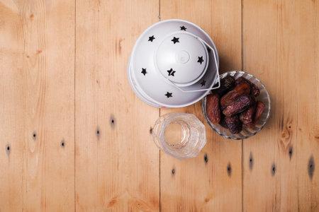 Traditional Islamic Ramadan or Ramazan Iftar food. Flat-lay of dates and fresh drinking water with lantern on wooden  background, top view. Ramadan muslim fasting month