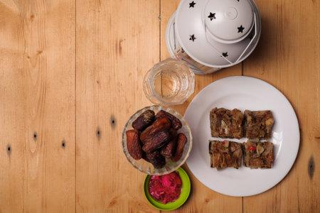 Traditional Islamic Ramadan or Ramazan Iftar food. Flat-lay of dates and fresh drinking water with Murtabak on wooden  background, top view. Ramadan muslim fasting month
