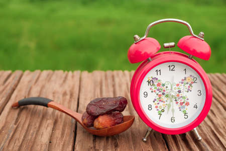 Dates fruits and alarm clock on old wooden table