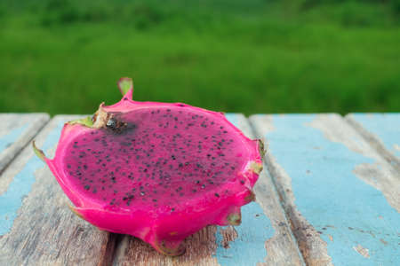 Dragon fruit on wooden table with green filed background, fresh fruit concept Stock fotó