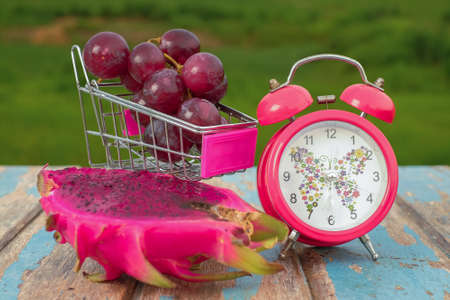 Red grapes , dragon fruit  and alarm clock on rustic wooden with green field background , fresh fruit concept