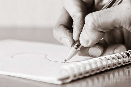 Notebook with question. Hand with pen. Image toned in black and white colors photo