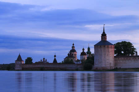 Russian orthodox monastery on the lake shore at sunrise with contrast sky photo