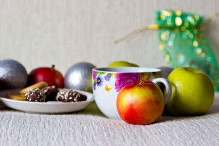Christmas composition close up: morning tea with cookies and candies, apples, silver and green christmas balls, gift photo