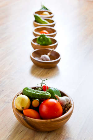 Fresh vegetables in wooden bowls in row. Focus on foreground. Vertical image photo