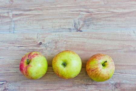 Three apples at wooden background photo