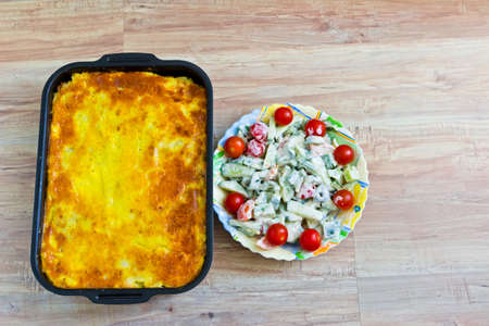 Potato casserole with eggs and meat. Fresh vegetable salad with sour cream photo