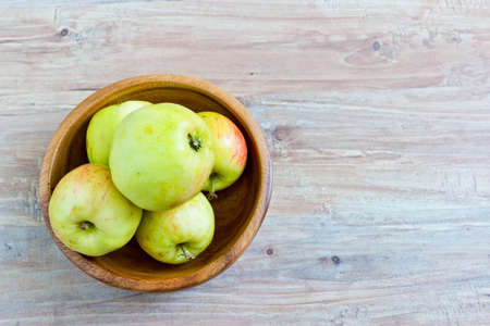 Fresh apples in wooden bowl. Horizontal image. Object at the left part of image photo