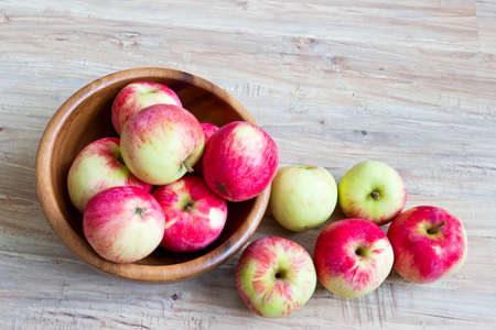 Fresh ripe apples in wooden bowl on wooden background photo