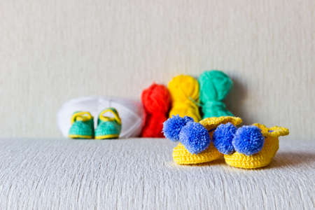 Colorful baby shoes with colored wool on white background close up photo