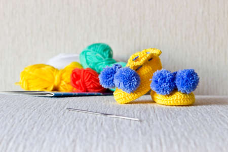 Colorful baby shoes with wool and knitting needles on white background close up photo