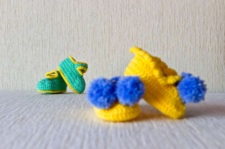 Homemade knitted small baby wool booties. Two couple. Selective focus photo