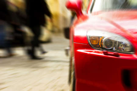 Fragment of red sport car in sunlight. Blurred background photo