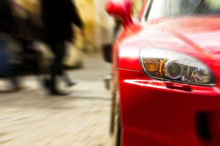 dream car: Fragmento de coche deportivo rojo en la luz del sol. Fondo borroso