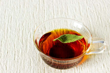 Fresh strong black tea with mint leaf in glass cup on textured linen background