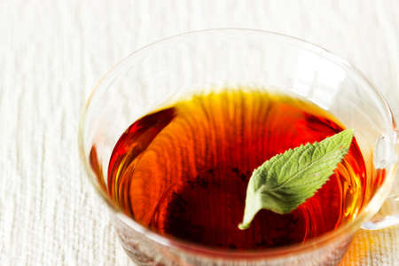 Fresh strong black tea with mint leaf in glass cup on textured linen background photo