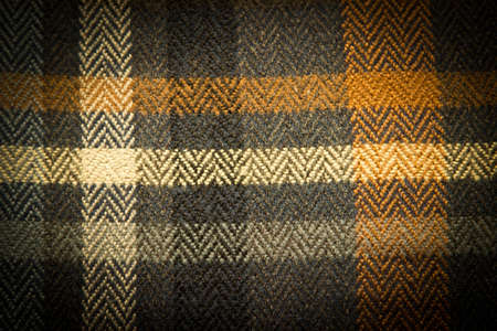textile image: Abstract textile colorful checkered background. Horizontal image with dark vignette