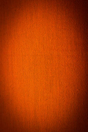 textile image: Abstract textile orange background with dark vignette. Vertical image