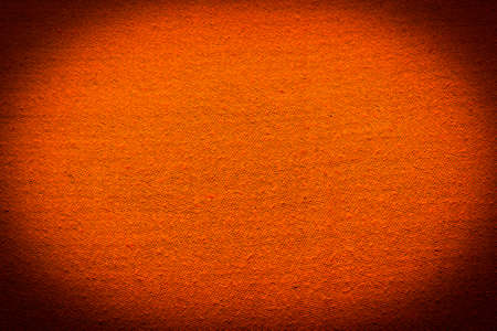 textile image: Abstract textile orange background. Image with dark vignette effect