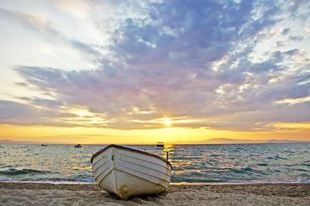 Beautiful sunrise over Aegean sea with lonely fishing boat on beach. Halkidiki, Greece photo