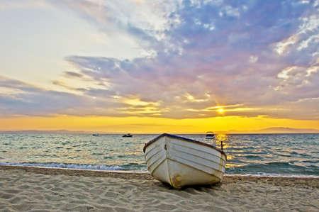 Beautiful sunrise over Aegean sea with lonely fishing boat photo