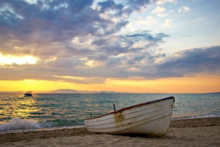 Beautiful sunrise over Aegean sea with lonely fishing boat on beach photo
